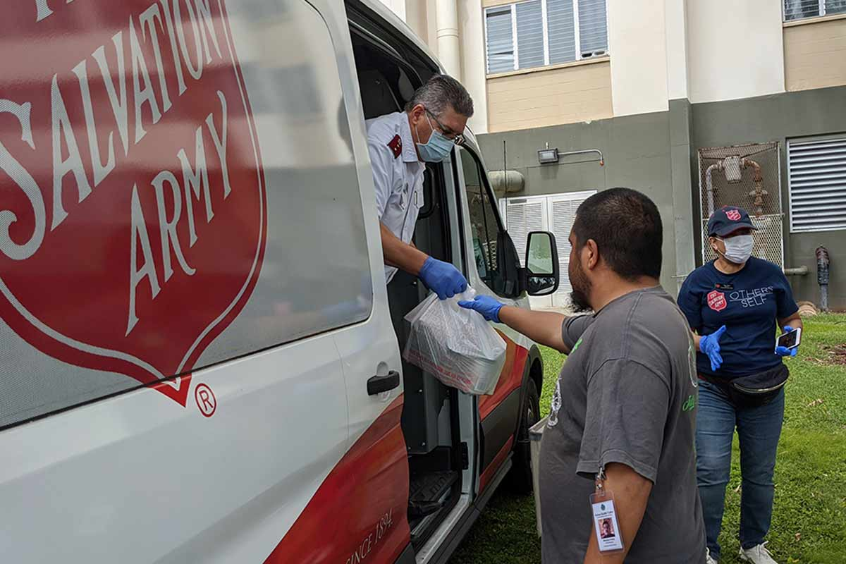 Salvation Army officer hands out bags of food at KPT
