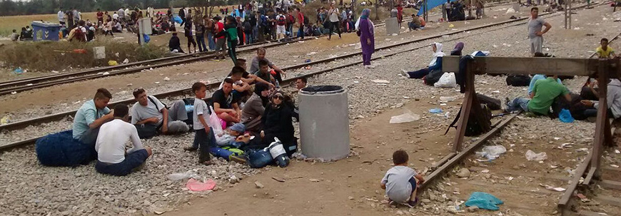rufugees rest along railroad tracks