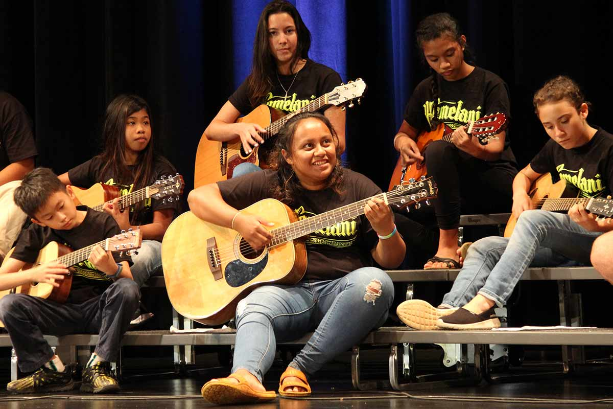 Camp Homelani youth playing guitar at Kroc Center Hawaii