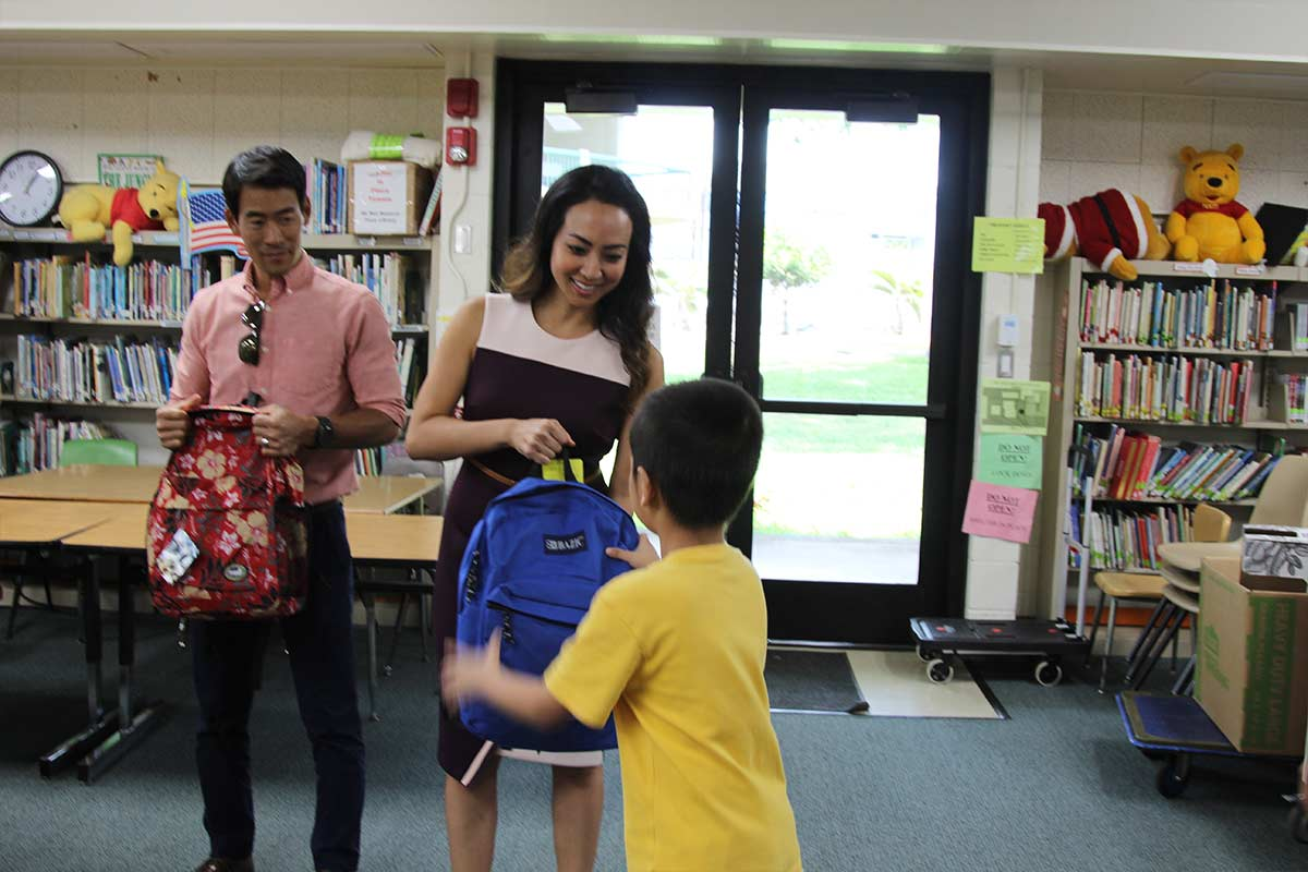 Echelon Member Camy Yano handing school supplies to student