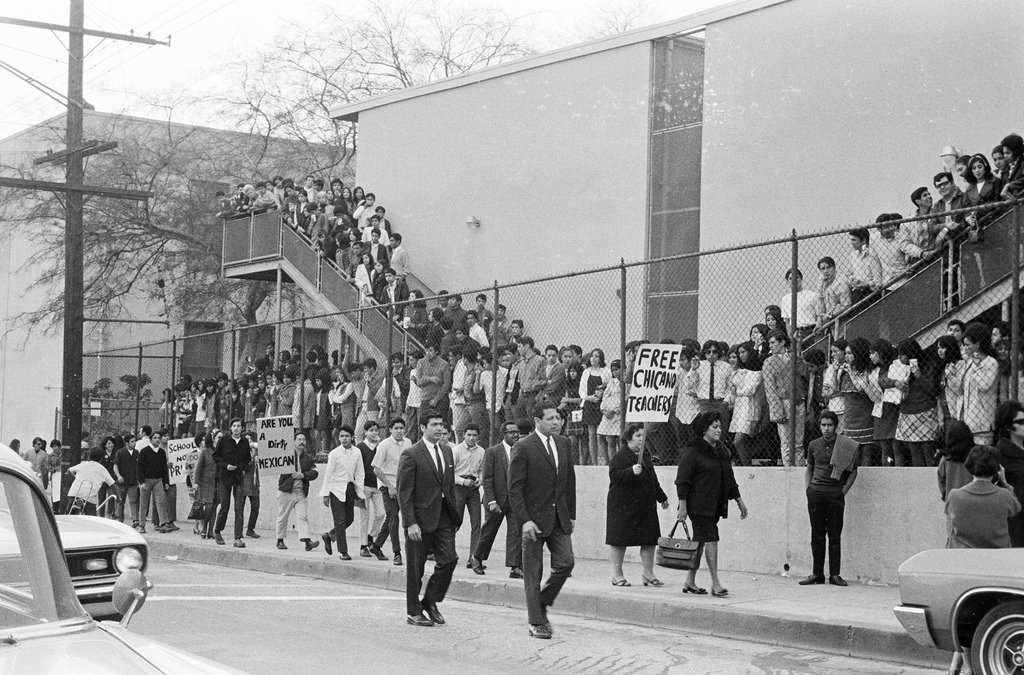 The Roosevelt High School fence separates students from parents and community. But both are united in their aim of having better schools with a relevant curriculum and more Chicano teachers and administrators.