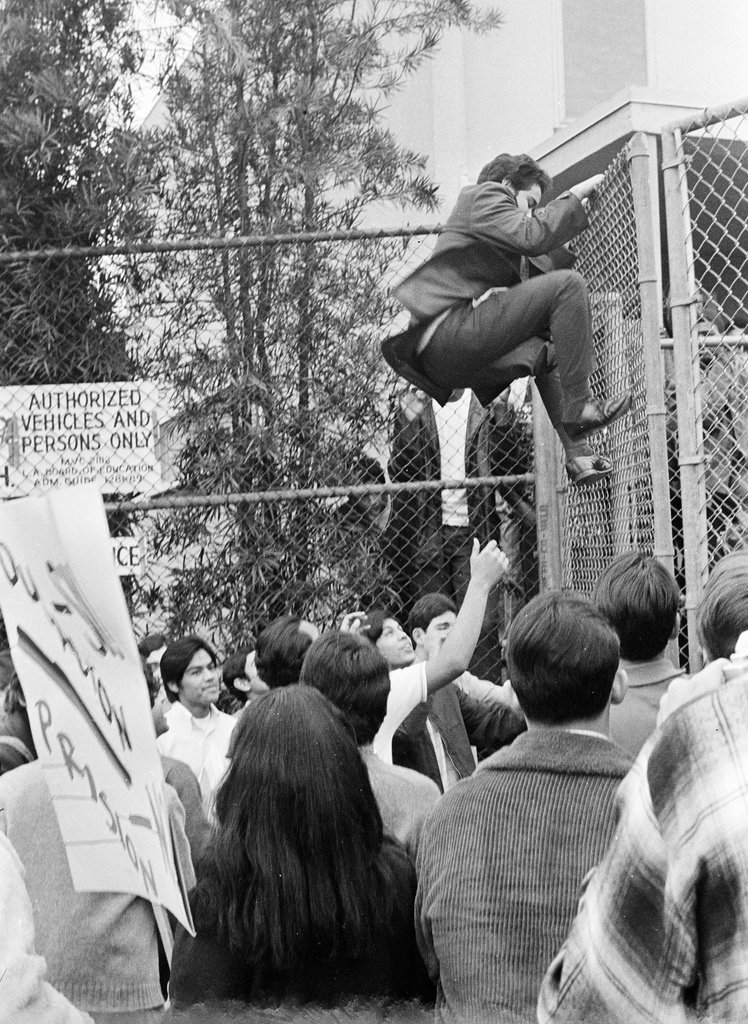 A Roosevelt High School student walking out by climbing over the fence.