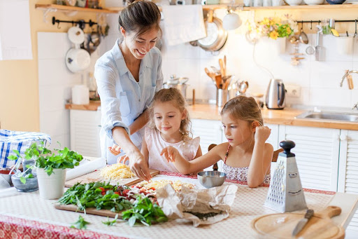 Woman prepping food with two girls with autism.