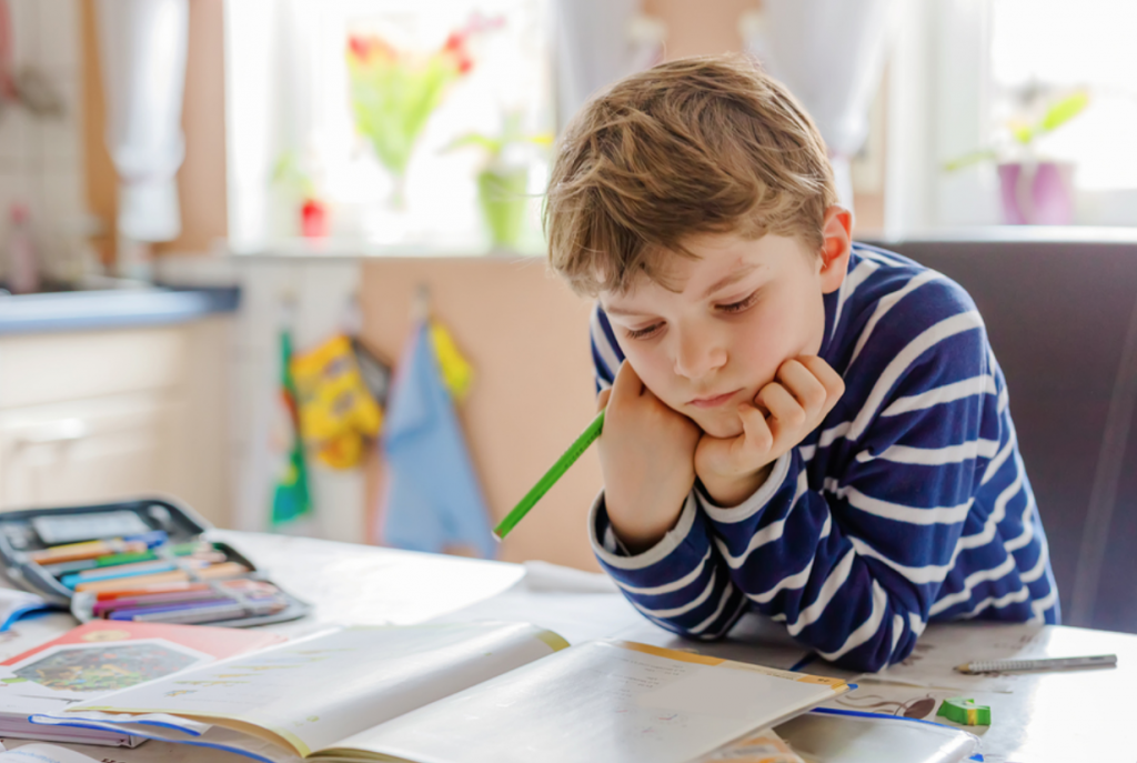 A photo of a child with autism studying for school.