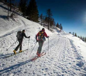 Ski touring uphill on well trodden path | Shutterstock image