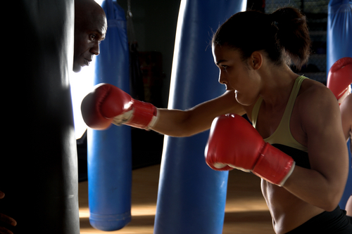 Boxer punching bag with trainer behind her