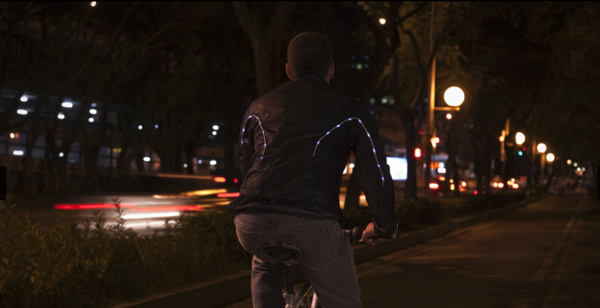 Man riding bike with NeonMan jacket from AiQ Smart Clothing