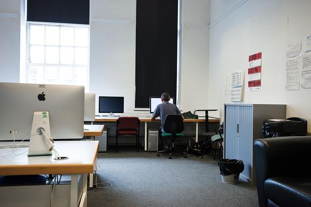 office with empty desks and computers with one lone worker