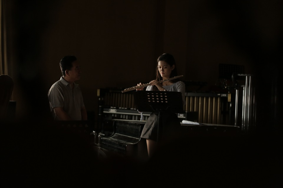 man tutoring one oh his music students in a dark music room