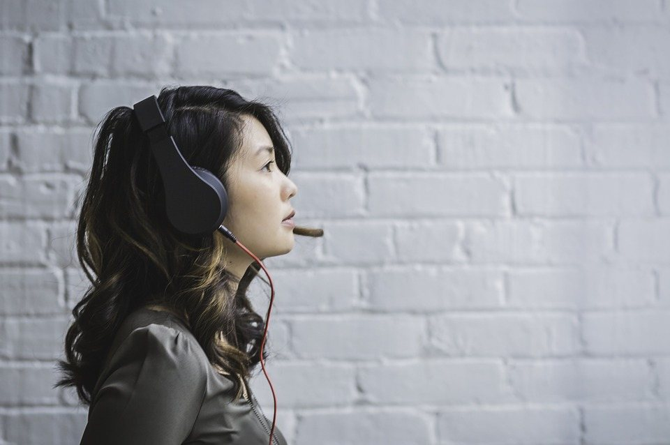 woman wearing conference call headset in front of white brick wall
