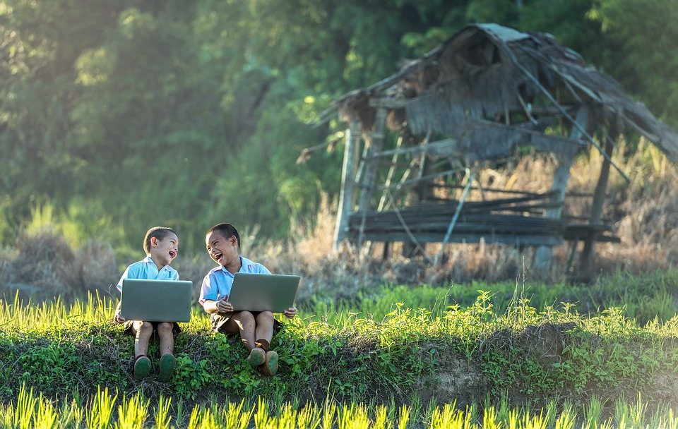 two children sitting outdoors with laptops on a conference call