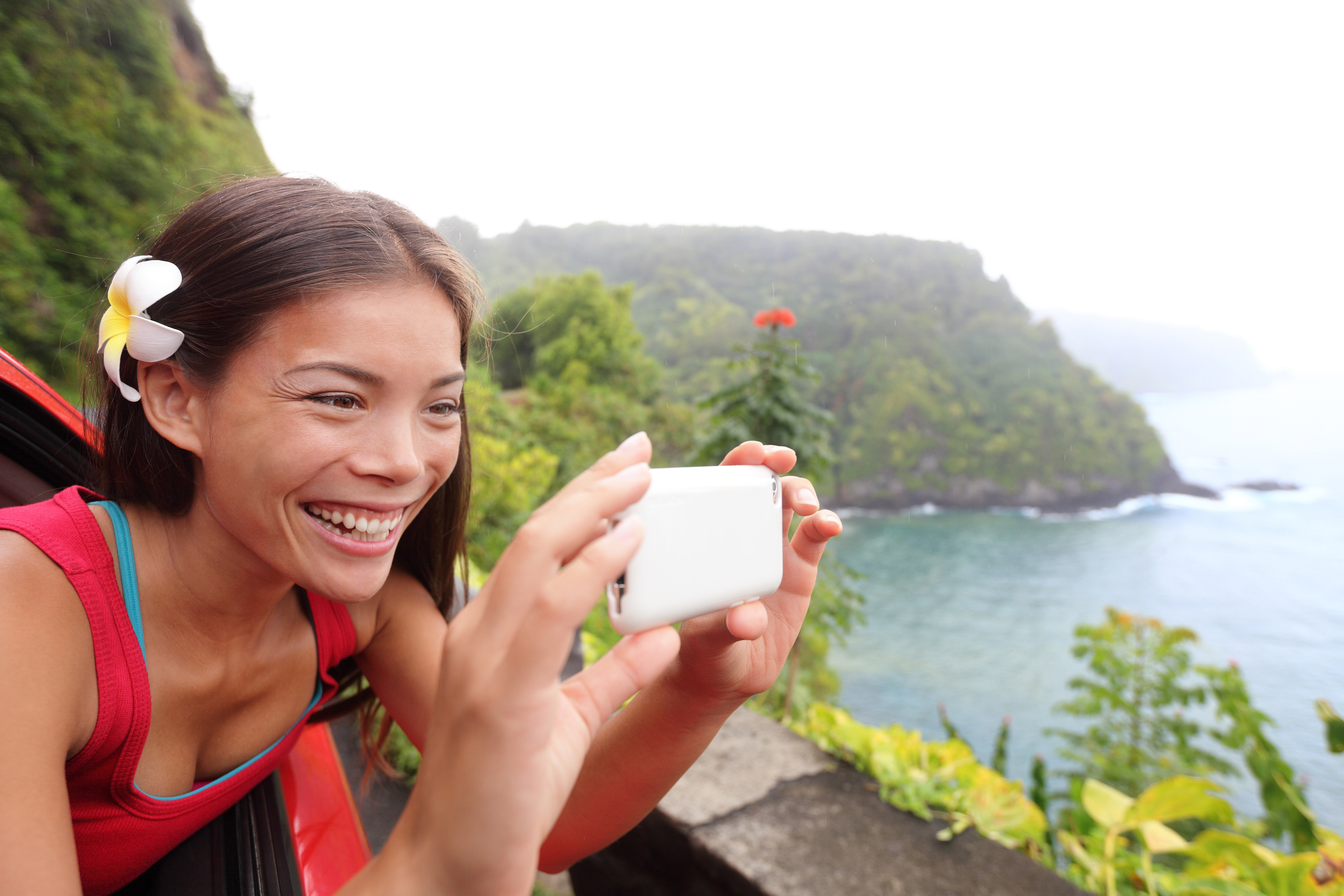 Tourist on Hawaii taking photo with camera phone during car road trip on the famous Road to Hana