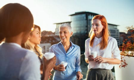 Business women having an outdoor meeting on the rooftop while drinking coffee.