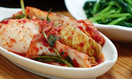 white oval plate filled with kimchi or spicy fermented cabbage beside a plate of boiled leafy greens, 7 Sources of Probiotics that Aren't Dairy