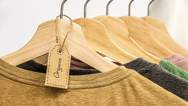 How-To-Shop-For-Ethical-Fashion-On-A-Budget-clothes-hanging-on-a-rack-with-the-tag-organic