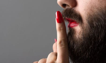 Bearded Man with Red Lipstick on His Lips and Nail Polish Making Silence Gesture
