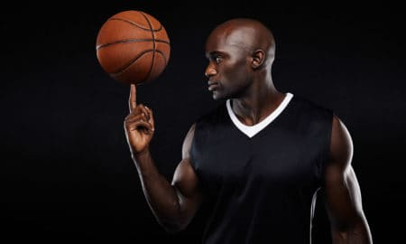 Portrait of young african athlete balancing basketball on his finger against black background. Focused basketball player.
