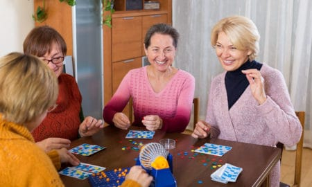 Several happy female pensioners playing board game in room at the home