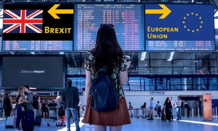woman standing at the airport loloking at the brexit