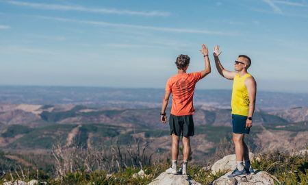 two-men-high-fiving-on-top-off-mountain-rockay