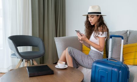 cute girl on phone while sitting on couch with luggage