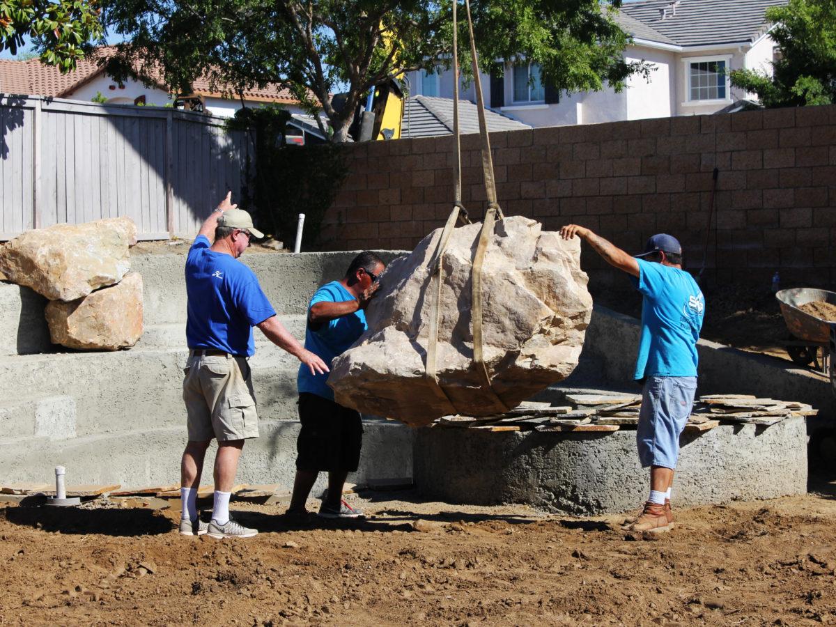 Crane placing boulder on landscape