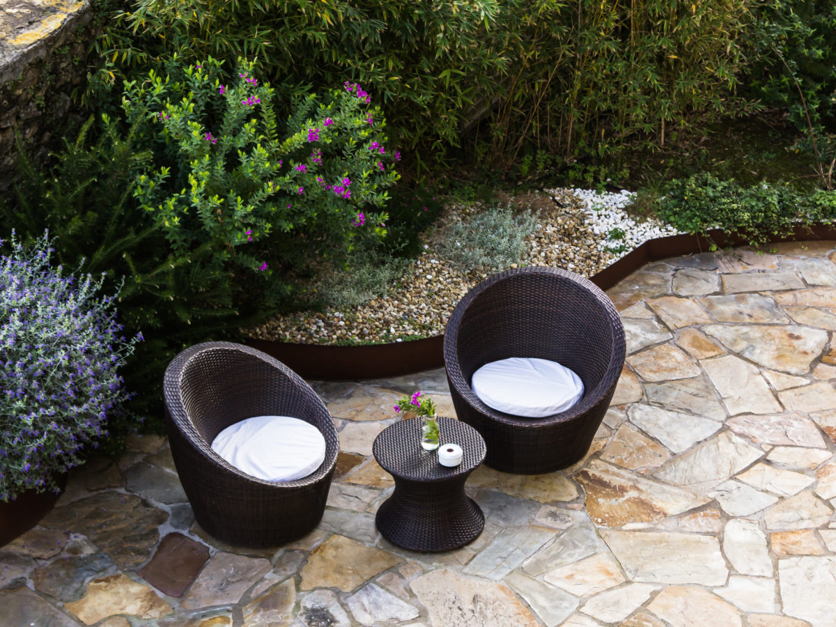 Flagstone patio in backyard with furniture and crushed rock