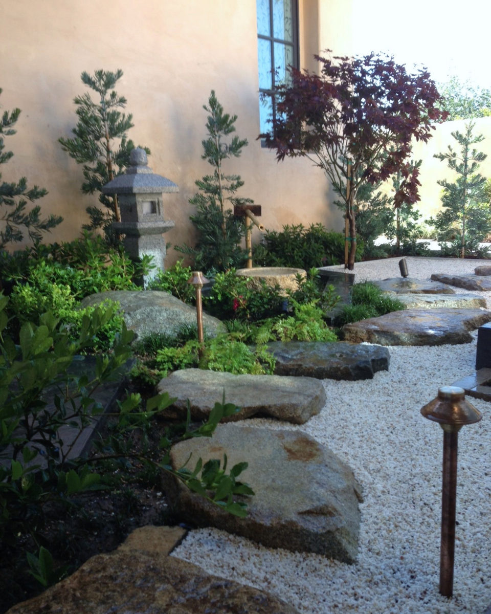 Backyard zen garden pathway with stepping stones and boulders