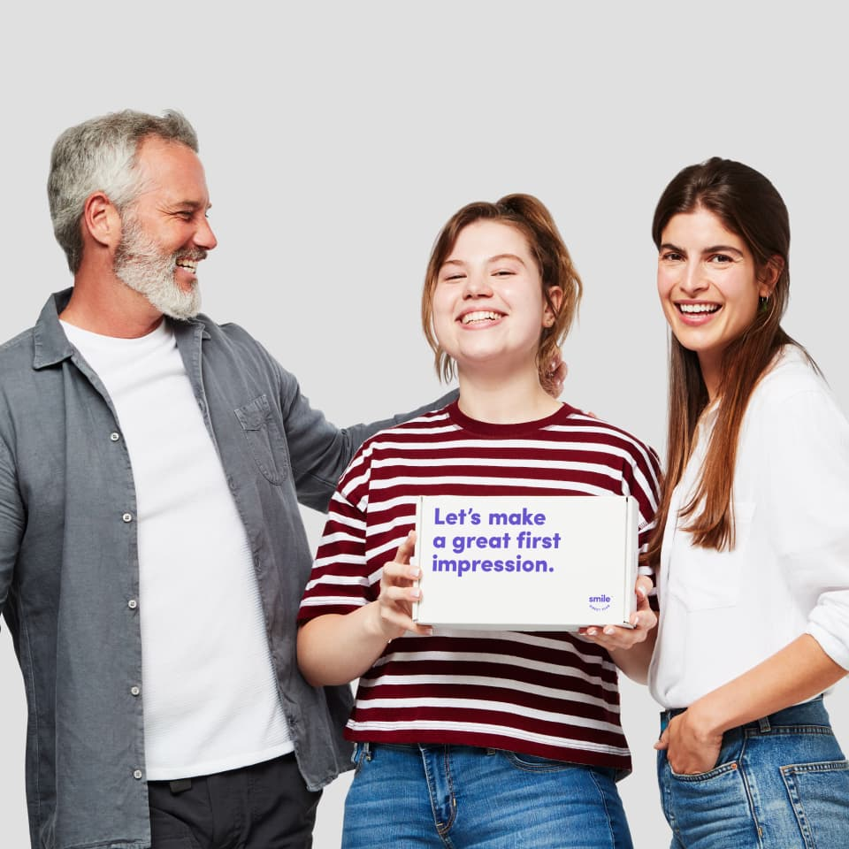 A family smiling and holding a Smile Direct Club impression kit